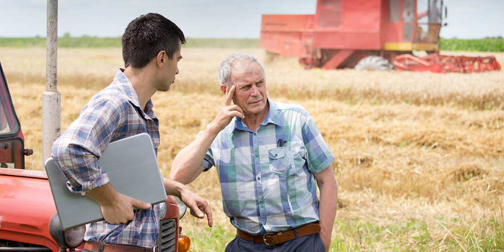 young man with laptop talking with farmer
