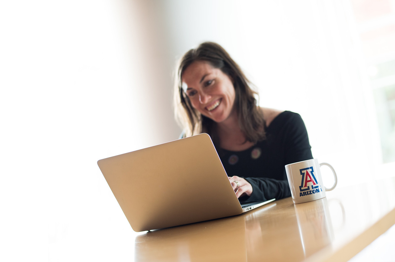 University of Arizona, woman on laptop, UArizona coffee mug