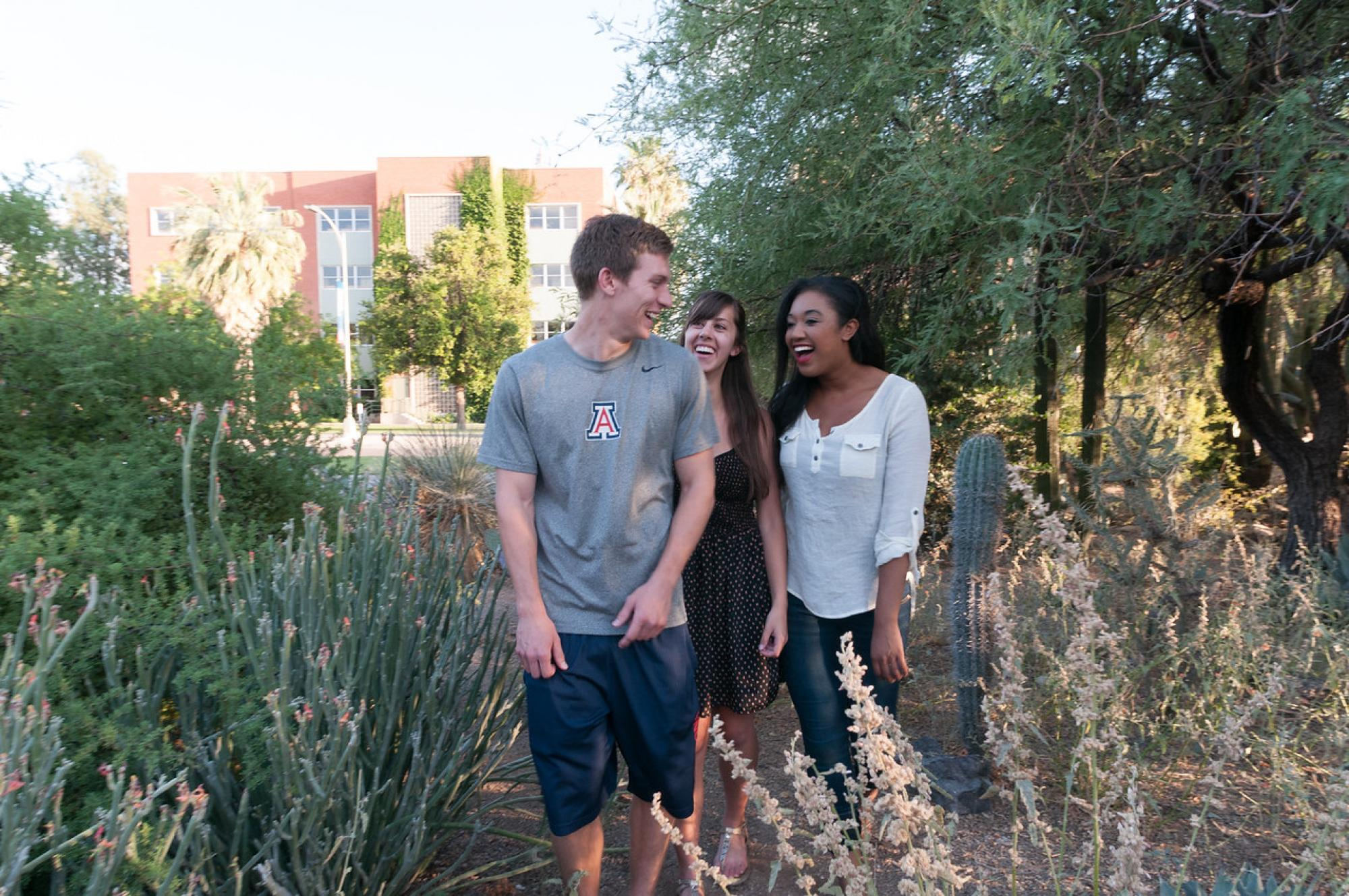 three smiling students walk through cactus garden, University of Arizona, Tucson
