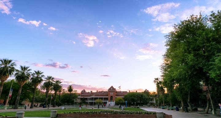 View of blue sky and UArizona Old Main building and green grassy area